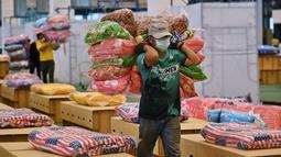 Pekerja menyiapkan kasur dan selimut untuk tempat tidur kardus di rumah sakit lapangan Covid-19 di dalam gudang Bandara Internasional Don Mueang di Bangkok, Selasa (27/7/2021). Thailand menghadapi rekor jumlah kasus virus corona di tengah kampanye vaksinasi yang lambat. (Lillian SUWANRUMPHA/AFP)