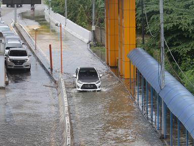 Sejumlah kendaraan melintasi Gerbang Tol Karang Tengah Barat 2 yang masih terendam banjir, Tangerang, Banten, Kamis (2/1/2020). Banjir setinggi betis orang dewasa masih menggenangi Gerbang Tol Karang Tengah Barat 2. (Liputan6.com/Angga Yuniar)