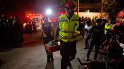 Tim penyelamat membawa peralatan menuju ke garasi parkir bawah tanah yang runtuh di sebuah kompleks di Mexico City (10/4). Petugas juga menggunakan anjing pelacak untuk mencari korban. (AP Photo/Rebecca Blackwell)