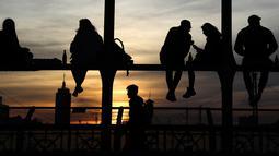 """Kaum muda menikmati matahari terbenam di jembatan 'Hackerbruecke' di Munich, Jerman, Minggu, (28/3/2021). Pada tahun 1890-94, jembatan ini digantikan oleh jembatan baru, yang dibangun oleh Maschinenfabrik Augsburg-Nürnberg (""""pabrik mesin Augsburg-Nuremberg""""). (AP Photo/Matthias Schrader)"""
