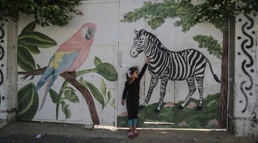 Seorang gadis Palestina menyentuh mural zebra di luar kebun binatang lokal yang ditutup di Rafah di Jalur Gaza selatan (26/5/2020). Kebun binatang itu ditutup selama liburan Idul Fitri karena pandemi virus coronavirus COVID-19. (AFP/Said Khatib)