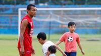 Pemain PSM Makassar, Ferdinand Sinaga, berlatih ditemani oleh buah hatinya. (Bola.com/Abdi Satria)