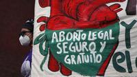 "Seorang perempuan memegang spanduk bertuliskan, dalam bahasa Spanyol, ""Aborsi legal, aman, dan gratis, legalkan dan dekriminalisasi aborsi sekarang, untuk kemerdekaan dan otonomi tubuh kita,"" (AP photo)"