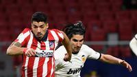 Penyerang Atletico Madrid, Luis Suarez (kiri) bersaing dengan gelandang Valencia, Carlos Soler pada jornada ke-20 Liga Spanyol di Wanda Metropolitano, Senin (25/1/2021) dini hari WIB. Atletico Madrid memetik kemenangan 3-1 atas Valencia. (PIERRE-PHILIPPE MARCOU/AFP)