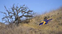 Nomor 24 Kobe Bryant ditempatkan di sepanjang jalan setapak yang mengarah ke lokasi kecelakaan helikopter yang menewaskan Bryant, putrinya Gianna, dan tujuh lainnya satu tahun lalu di Calabasas, California, Amerika Serikat, Selasa (26/1/2021). (AP Photo/Marcio Jose Sanchez)