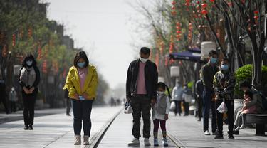 Orang-orang mengenakan masker membungkuk tiga menit selama peringatan nasional untuk memperingati korban meninggal dalam wabah virus coronavirus COVID-19 di sepanjang jalan bisnis di Beijing  (4/4/2020). (AFP/Wang Zhao)