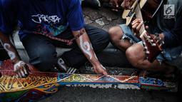 Eks pekerja PT Freeport Indonesia bermain musik saat menggelar aksi selama Car Free Day di kawasan Bunderan HI, Jakarta, Minggu (30/12). Aksi tersebut dilakukan protes mereka ke pemerintah. (Liputan6.com/Faizal Fanani)
