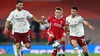 Gelandang Arsenal, Granit Xhaka, berebut bola dengan penyerang Liverpool, Diogo Jota, pada laga Piala Liga Inggris di Stadion Anfield, Jumat (2/10/2020) dini hari WIB. Arsenal menang 5-4 atas Liverpool lewat adu penalti. (AFP/Laurence Griffiths)