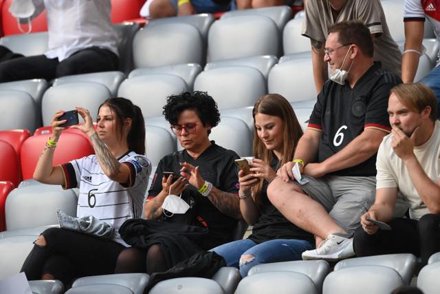 Jessica Kroos (tengah), istri dari gelandang Jerman Toni Kroos, mengambil gambar dengan ponselnya menjelang pertandingan sepak bola Grup F UEFA EURO 2020 antara Prancis dan Jerman di Allianz Arena di Munich pada 15 Juni 2021. (AFP/Pool/Matthias Hangst)
