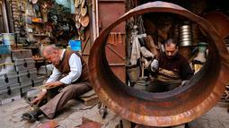 Para pedagang barang antik bekerja di toko mereka di Baghdad, Irak, Rabu (20/3). (AP Photo/Hadi Mizan)