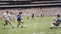 Penyerang Argentina, Diego Maradona, mencetak gol ke gawang Inggris pada laga perempat final Piala Dunia 1986 di Meksiko, (29/6/1986). (Photo by - / AFP)