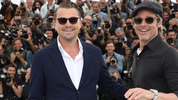 Aktor Brad Pitt dan Leonardo DiCaprio tersenyum saat berpose menghadiri pemutaran film 'Once Upon a Time in Hollywood' selama Festival Film Cannes Internasional ke-72 di Prancis (22/5/2019). (AP Photo/Vianney Le Caer)