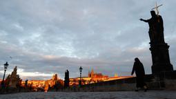 Seorang biarawati melintasi Jembatan Charles yang dibangun pada abad pertengahan di Praha, Republik Ceko, Kamis (8/10/2020). Republik Ceko pada Rabu (7/10) melaporkan sebanyak 5.335 kasus virus corona baru yang dikonfirmasi di negara itu, melampaui rekor hari sebelumnya. (AP Photo/Petr David Josek)