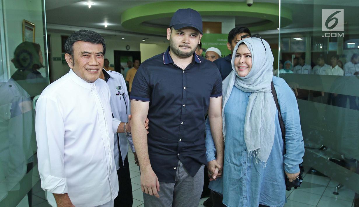 Ridho Rhoma (tengah) didampangi sang ayah, Rhoma Irama dan ibunya Ridho Marwah saat keluar dari RSKO, Jakarta, Kamis (25/01). Ridho Rhoma telah usai menjalankan rehabilitasi selama 10 bulan di RSKO. (Liputa6.com/Herman Zakharia)
