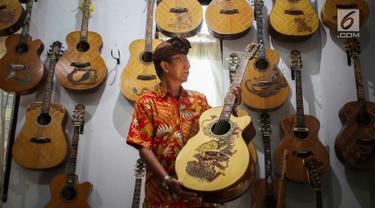 I Wayan Tuges melihat gitar yang telah diukirnya di workshop pembuatan gitar berlabel Blueberry di Jalan Baruna No. 5 Guwang, Sukowati, Bali, Senin (15/10). Gitar-gitar produksinya itu dibanderol seharga puluhan juta rupiah. (Liputan6.com/Angga Yuniar)