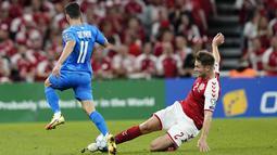 Pemain depan Israel, Manor Solomon berusaha melewati bek Denmark, Joachim Andersen selama pertandingan kualifikasi Grup F Piala Dunia FIFA Qatar 2022 di Kopenhagen (7/9/2021). Denmark menang telak ats Israel dengan skor 5-0. (Mads Claus Rasmussen/Ritzau Scanpix/AFP)