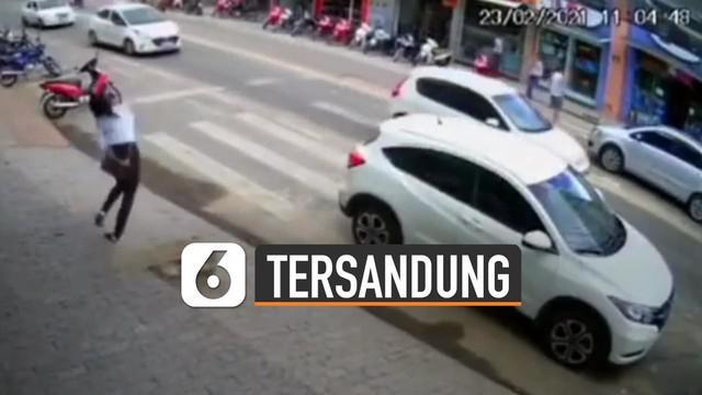 Terekam kamera CCTV seorang perempuan tersandung dan jatuh di zebra cross tengah jalan.