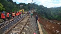 Petugas PT KAI memperbaiki rel yang longsor di Kampung Maseng Bogor. (Achmad Sudarno/Liputan6.com)
