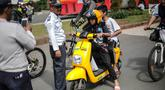Petugas Dishub mensosialisasikan kepada pengendara sepeda motor listrik Migo saat melintasi CFD di kawasan Bundaran HI, Jakarta, Minggu (17/2). Penyewa sepeda motor listrik dihimbau untuk tidak melintasi jalan raya.(Www.sulawesita.com)