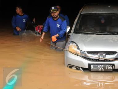 Petugas berusaha mengevakuasi mobil dari parkir basement sebuah pertokoan di Jalan Kemang Raya, Minggu (28/8). Sejumlah kendaraan terendam air di kawasan Kemang Raya pasca hujan deras di Jakarta pada Sabtu (27/8). (Liputan6.com/Helmi Fithriansyah)