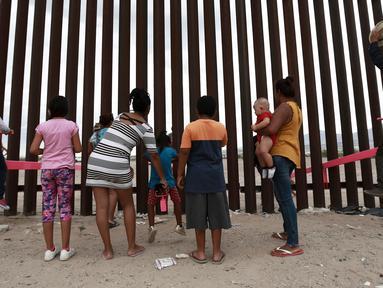 Anak-anak bermain jungkat-jungkit yang dipasang di antara pagar pemisah Meksiko dengan Amerika Serikat, Ciudad de Juarez, Meksiko, Minggu (28/7/2019). Jungkat-jungkit tersebut dirancang seorang profesor arsitektur California, Ronald Rael. (AP Photo/Christian Chavez)