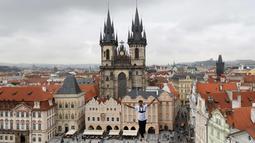 Atlet menyeimbangkan tubuhnya saat berjalan di atas tali yang membentang di Old Town Square, Praha, Republik Ceko, (25/9). Pertunjukan tersebut merupakan bagian kampanye dukungan orang-orang yang hidup dengan diabetes. (AP Photo/Petr David Josek)