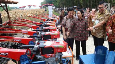 Menteri BUMN Rini Soemarno (tengah) dan Dirut BNI Achmad Baiquni (kanan) meninjau perlengkapan pendukung produksi pertanian di Tuban, Jawa Timur, Jumat (9/3). Perlengkapan itu akan dipakai pada lahan Perhutanan Sosial. (Liputan6.com/Angga Yuniar)
