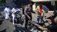 Anggota polisi menggeledah motor tamu pengunjung yang datang ke Mapolda Jawa Tengah, Kota Semarang, Senin (14/5).Tak ingin kecolongan, Mapolda Jateng memperketat pengamanan menyusul aksi teror bom yang bertubi-tubi. (Liputan6.com/Gholib)