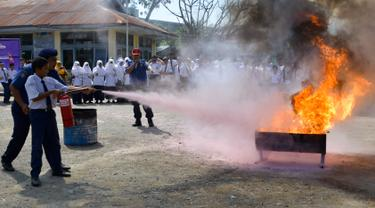 Seorang siswa berlatih memadamkan api menggunakan alat pemadam di Banda Aceh, Senin (11/11/2019). Sebanyak 439 pelajar mendapat pembekalan cara pencegahan pemadaman api akibat kebakaran dari petugas Dinas Pemadam Kebakaran dan Penyelamatan Kota Banda Aceh. (CHAIDEER MAHYUDDIN/AFP)