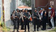 Polisi bersenjata berjaga-jaga saat berlangsungnya olah TKP di rumah terduga teroris di Nanggewer, Cibinong, Bogor, Jawa Barat, Sabtu (18/5/2019). Densus 88 Antiteror Mabes Polri menggelar olah TKP di rumah terduga teroris E alias Abu Rafi alias Pak Jenggot (51). (merdeka.com/Imam Buhori)