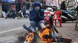 Seorang pria menghangatkan diri di depan kayu bakar saat hari musim dingin di Hanoi, Vietnam, Jumat (8/1/2021). Vietnam tahun ini diperkirakan mengalami musim dingin yang lebih dingin dari biasanya ketika suhu permukaan laut Samudra Pasifik turun, membentuk fenomena La Nina. (Nhac NGUYEN/AFP)