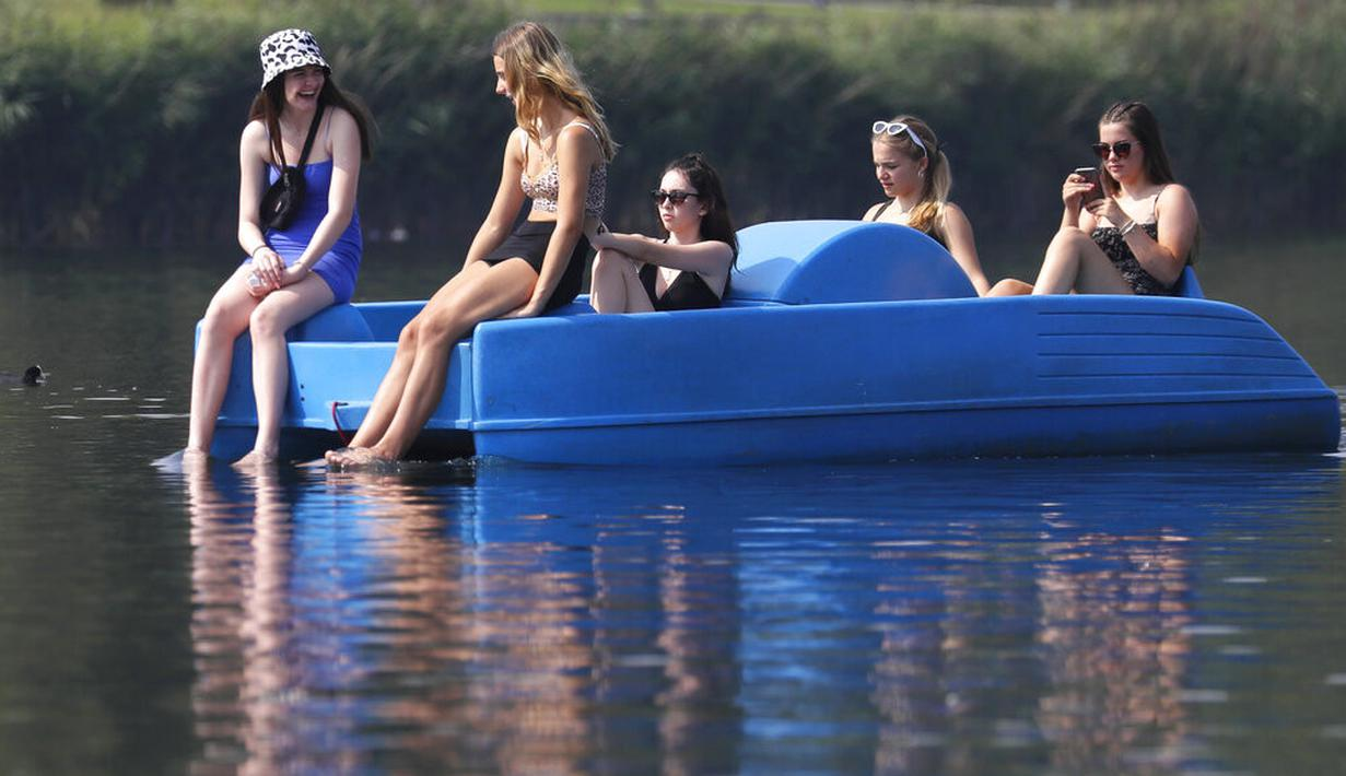 Sejumlah wanita bersantai di perahu kayuh di The Serpentine di Hyde Park di London, Rabu, (12/8/2020). Peringatan badai masih berlaku untuk sebagian besar Inggris pada hari Rabu, sementara suhu tinggi diperkirakan lagi di banyak bagian Inggris. ( AP Photo / Kirsty Wigglesworth)