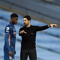 Pemain Arsenal, Thomas Partey, mendengarkan instruksi dari sang manajer, Mikel Arteta, ketika akan menjalani debut bersama The Gunners dalam laga kontra Manchester City, Minggu (18/10/2020). (AFP/MICHAEL REGAN)