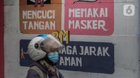 Pengendara motor melintasi mural bertuliskan protokol kesehatan COVID-19 di Kawasan Kota Bambu, Jakarta, Selasa (20/10/2020). Sehingga total kasus Covid-19 di Indonesia menjadi 373.109 kasus dengan DKI Jakarta tetap menduduki peringkat pertama dengan 1.000 kasus. (Liputan6.com/Johan Tallo)