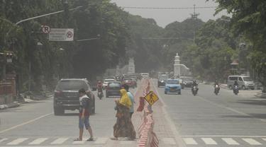 Orang-orang menyeberang jalan yang tertutup abu setelah letusan Gunung Merapi di Solo (3/3/2020). Gunung paling aktif di Indonesia tersebut meletus pada 3 Maret pukul 05.22 WIB dengan tinggi kolom 6.000 meter. (AFP Photo/Dika)