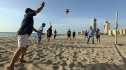Orang-orang bermain voli pantai sembari menunggu waktu berbuka puasa selama bulan suci Ramadan, meskipun lockdown karena pandemi COVID-19, di ibu kota Tripoli, Libya pada Jumat (8/5/2020). (Photo by Mahmud TURKIA / AFP)
