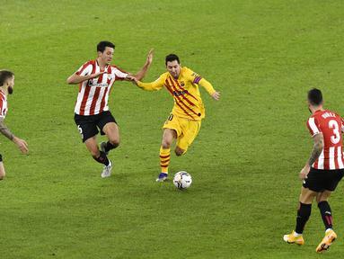 Pemain Barcelona Lionel Messi (kedua kanan) menggiring bola melewati tiga pemain Athletic Bilbao pada pertandingan Liga Spanyol di Stadion San Mames, Bilbao, Spanyol, Rabu (6/1/2021). Barcelona menang 3-2 dengan dua gol dari Lionel Messi. (AP Photo/Alvaro Barrientos)