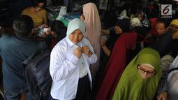 Seorang anak mencoba baju seragam sekolah baru di salah satu kios di Jalan Pengadilan, Bogor, Rabu (11/7). Menjelang dimulainya tahun ajaran baru, para orang tua disibukan belanja kelengkapan sekolah anak mereka. (Merdeka.com/Arie Basuki)