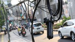 Instalasi kabel menjuntai ke trotoar di Jalan Kyai Maja, Jakarta, Rabu (10/4). Selain menganggu kenyamanan pejalan kaki, kondisi instalasi kabel yang semrawut tersebut juga berbahaya apabila mengandung aliran listrik. (Liputan6.com/Immanuel Antonius)