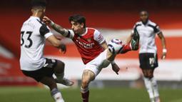 Bek Arsenal, Hector Bellerin (tengah) berebut bola dengan bek Fulham, Antonee Robinson dalam laga lanjutan Liga Inggris 2020/2021 pekan ke-32 di Emirates Stadium, Minggu (18/4/2021). Arsenal bermain imbang 1-1 dengan Fulham. (AP/Julian Finney/Pool)