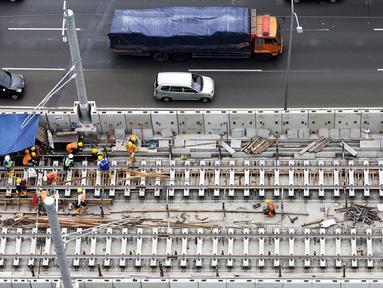 Pekerja menyelesaikan rel jalur layang mass rapid transit (MRT) yang melintasi tol Jakarta Outer Ring Road (JORR) TB Simatupang, Jakarta, Sabtu (21/4). Jalur MRT  memiliki 7 stasiun layang dan 6 stasiun bawah tanah. (Liputan6.com/Fery Pradolo)