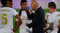 Pelatih Real Madrid, Zinedine Zidane, dan para pemainnya pada laga kontra Alaves di Stadion Alfredo Di Stefano, Sabtu (11/7/2020) dini hari WIB. (AFP/Gabriel Bouys)