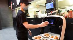 Pelayan memasukkan nomor meja untuk pengantaran robot di restoran Asia di Wina, Austria, Kamis (28/5/2020). Restoran tersebut menggunakan robot untuk mengantar makanan guna mengurangi kontak yang tidak diperlukan antara pelayan dan pelanggan di tengah pandemi virus corona COVID-19. (Xinhua/Guo Chen)
