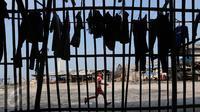 Seorang anak berlari di pemukiman kumuh, Muara Angke, Jakarta, Rabu (3/8). Badan Pusat Statistik DKI Jakarta melansir angka kemiskinan Ibu Kota pada bulan Maret 2016 mencapai 384,3 ribu orang atau 3,75%. (Liputan6.com/Angga Yuniar)
