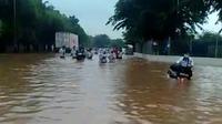 Sejumlah karyawan pabrik menerobos banjir setinggi lebih dari satu meter di depan PT Panasonic Gobel, Cikarang, Kabupaten Bekasi. (Foto: Istimewa)