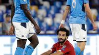 Penggawa Liverpool, Mohamed Salah duduk di atas lapangan melihat pemain Napoli, Kalidou Koulibaly pada matchday pertama Grup E Liga Champions di Stadion San Paolo, Selasa (17/9/2019). Juara bertahan Liverpool secara mengejutkan menyerah dua gol tanpa balas dari Napoli. (AP Photo/Gregorio Borgia)
