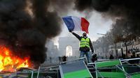 """Demonstran mengibarkan bendera Prancis saat kerusuhan menentang kenaikan harga bahan bakar di Paris, Prancis, Sabtu (24/11). Demonstrasi terjadi oleh dorongan gerakan """"rompi kuning"""". (AP Photo/Michel Euler)"""