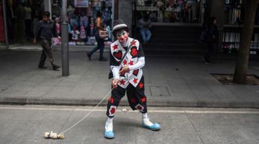 Seorang badut berpose selama parade pada Konvensi Badut Regional ke-5 di kota Guatemala, Rabu (19/9). Dalam acara tersebut, dengan kostum warna-warninya mereka berparade menelusuri jalanan pusat sejarah Guatemala City. (AFP / Johan ORDONEZ)