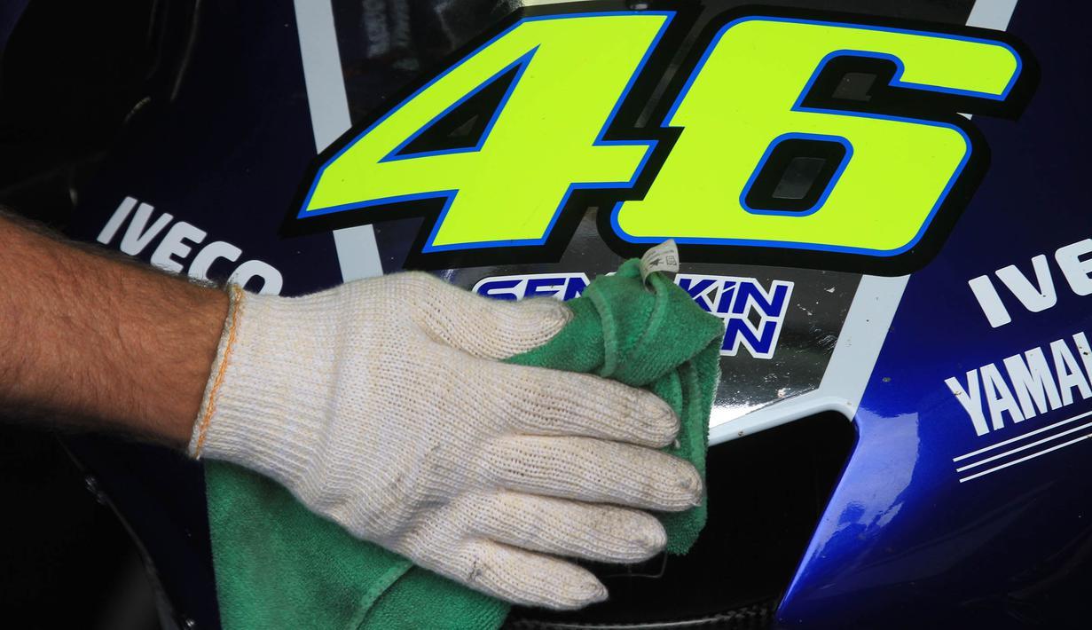 Pekerja membersihkan motor milik pebalap MotoGP asal Itali, Valentino Rossi. Bersama Yamaha, juara dunia sembilan kali itu menggunakan motor dengan dominasi warna biru. (AFP Photo/Radek Mica)