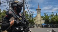 Polisi berjaga di luar gereja setelah ledakan di Makassar (28/3/2021). Berdasarkan informasi yang dihimpun di lokasi, garis polisi pun telah dibentangkan oleh petugas. Petugas masih bersiaga mengamankan lokasi. (AFP/Indra Abriyanto)